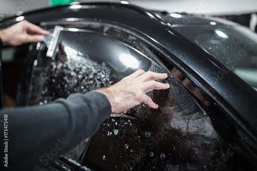 Fotografía  Car tinting - Worker applying tinting foil on car window.