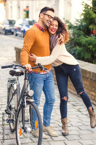Fototapeta Szczęśliwi potomstwa dobierają się z bicyklem na pogodnym jesień dniu w mieście.