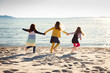 Three girls running hand in hand on a sandy beach