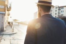 Rear View Of Man In Boater Strolling Along Sunlit Street