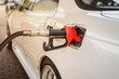 red refueling nozzle is inserted in the tank car at a gas station