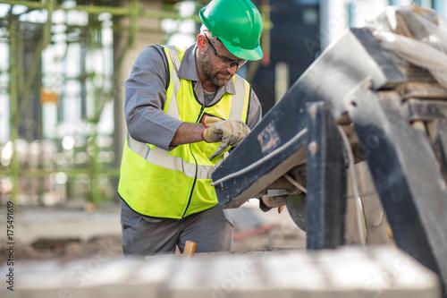Fototapeta Construction worker using heavy machinery