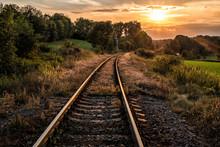 Railway Tracks, Trees And Sunset