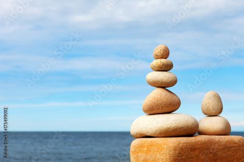 Plakat Kamienie balansują na tle niebieskie niebo i morze