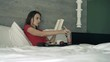 Woman reading book during breakfast in bed at home