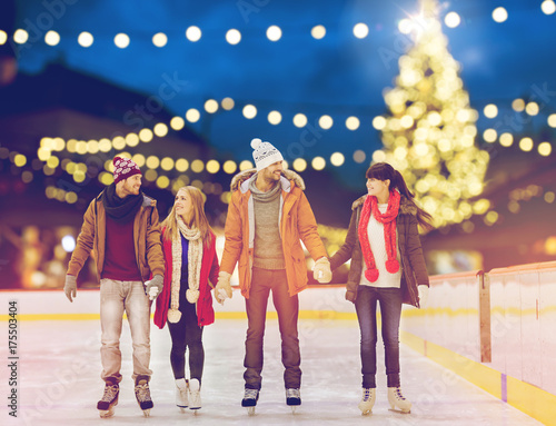 happy friends at christmas skating rink