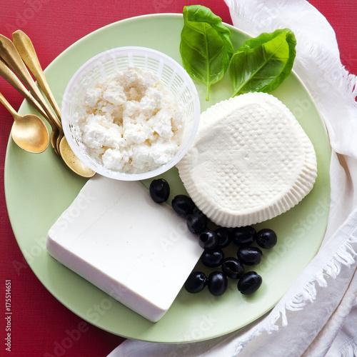 Plakat grupa białych serów: ricotta, sycylijska primosale i owczy ser na talerzu. przekąski z oliwkami