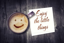 Enjoy The Little Things Inspirational Note On Paper Card With Coffee Cup On Wooden Background