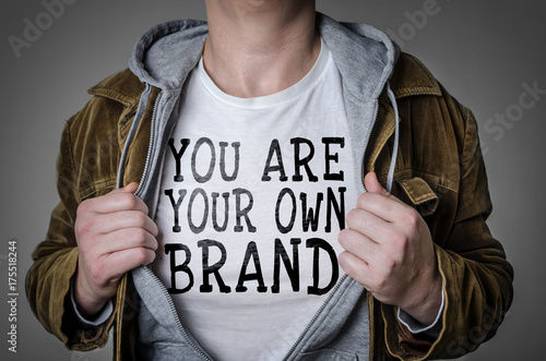 Obraz Man showing You Are Your Own Brand tittle on t-shirt. Personal branding concept. - fototapety do salonu