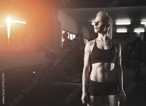 Sport fitness woman in gym young woman lifting the dumbbells