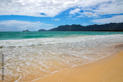 Receding waves under dense clouds at Bellows Beach, Oahu, Hawaii