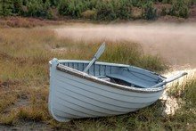 Rowboat At Edge Of Mist-covered Pond In Alaska