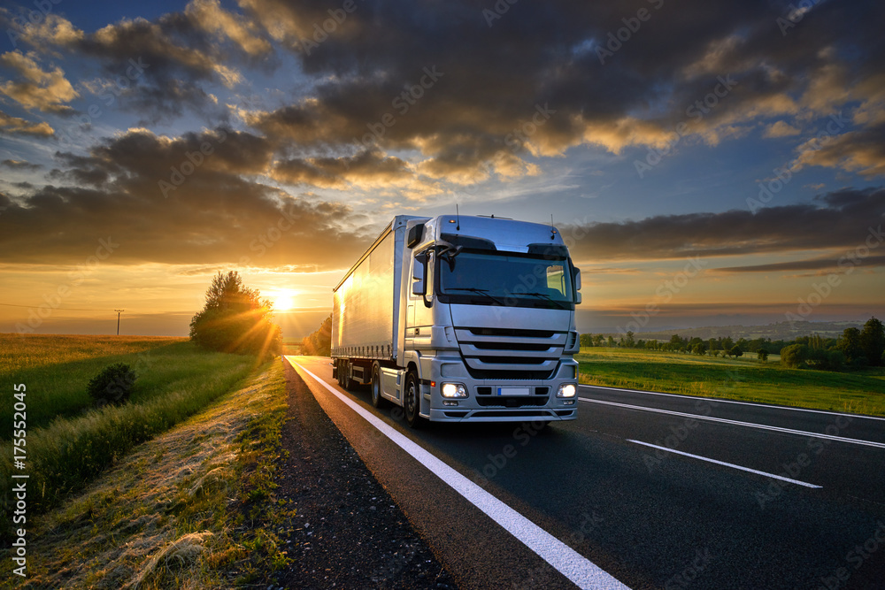 Fototapeta Truck driving on the asphalt road in rural landscape at sunset with dark clouds