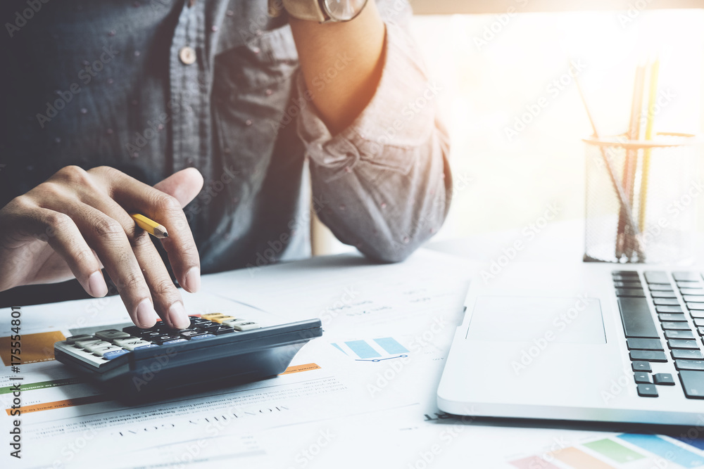 Fototapeta Close up a man working about financial with calculator at his office to calculate expenses, Accounting concept