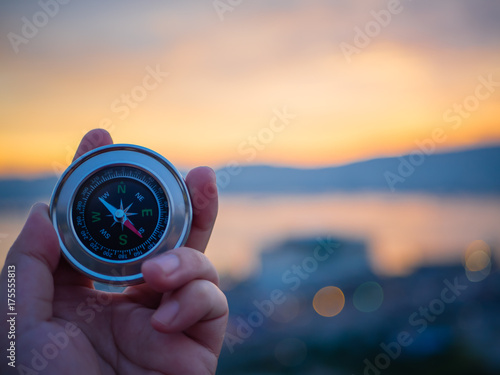 Photo Closeup hand holding compass with  mountain and sunset sky background