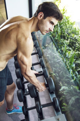Young handsome muscular man exercising in the gym. Picking dumbbell from weight rack.