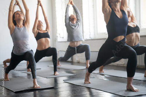 Fotobehang School de yoga Group of young sporty attractive people practicing yoga lesson with instructor, standing together in Virabhadrasana 1 exercise, Warrior one pose, working out, full length, studio background, close up