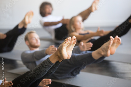 Recess Fitting Yoga school Group of young sporty people practicing yoga lesson with instructor, stretching in Paripurna Navasana exercise, balance pose, working out, indoor close up image, studio, focus on feet