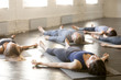 Leinwandbild Motiv Group of young sporty people practicing yoga lesson in gym, lying in Corpse exercise doing Savasana pose, friends relaxing after working out in sport club, indoor image. Wellbeing and wellness concept