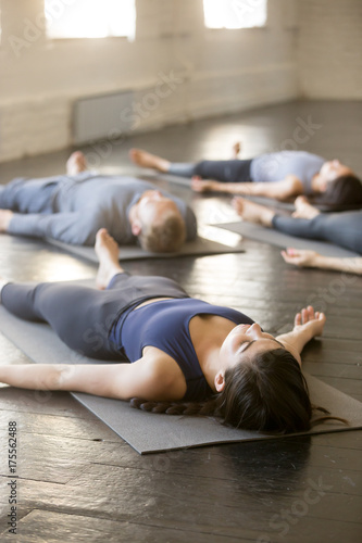 Photo  Group of young sporty people practicing yoga lesson with instructor in gym, lyin