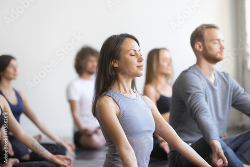 Group of young people, sporty students practicing yoga lesson with instructor, sitting and meditating with closed eyes in Padmasana exercise, Lotus pose, friends working out in club, studio background