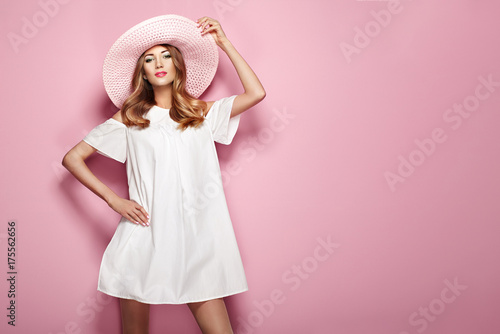 Fotografija  Blonde Young Woman in elegant white Dress and Summer Hat