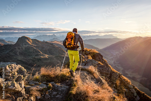 Photographie Mountaineer hiking in the mountains in morning light
