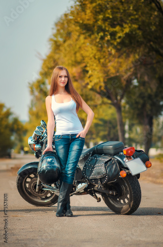 Plakat Piękna młoda dziewczyna blisko motocyklu