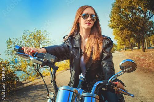 Fototapeta młoda kobieta w skórzanej kurtce i niebieskie dżinsy w okularach na motorze