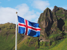 Flag Of Iceland Against The Background Of Green Mountains And Blue Sky