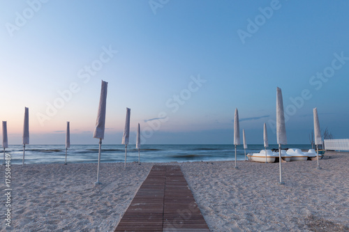 White umbrella on the morning beach