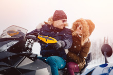 Snowmobile. A Couple Of Girlfriends And A Guy On A Snowmobile Laugh. Concept Travel In Winter.