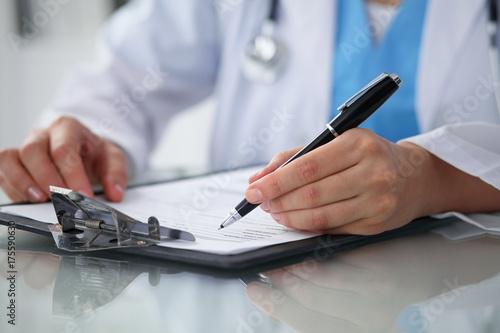 Plakat Doktorska kobieta wypełnia w górę medycznej formy podczas gdy siedzący przy stołem, zakończenie ręki
