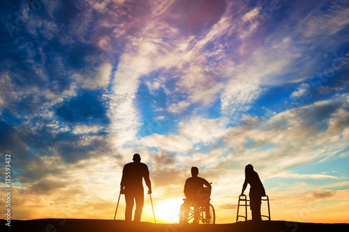 Photo  Three disabled people at the sunset.