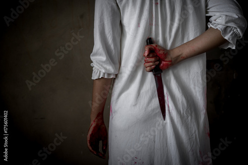 Closeup Ghost woman holding knife hidden for kill with blood violence in house of ruin, nightmare, horror of scary fear on hell is monster devil in halloween festival, copy space the left Canvas Print
