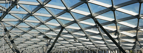 Fotografie, Obraz The glass ceiling of the modern building supports a steel beams grid