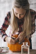 Woman Decorating Pumpkin Using Decoupage Technique