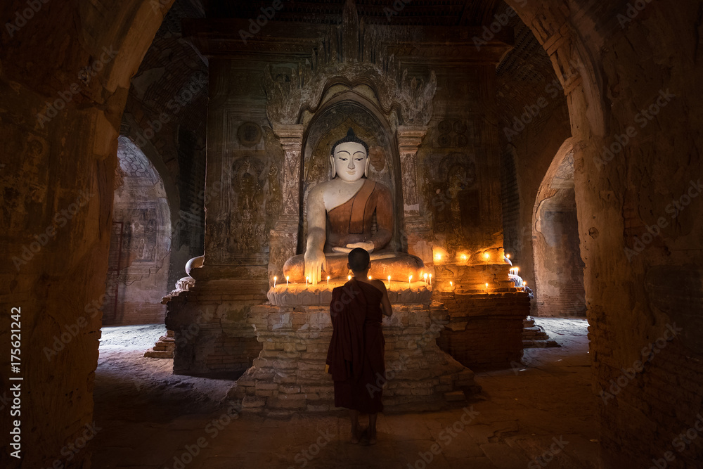 Fototapeta Young novice monk praying with candles in front of buddha statue inside old pagoda, Bagan Myanmar