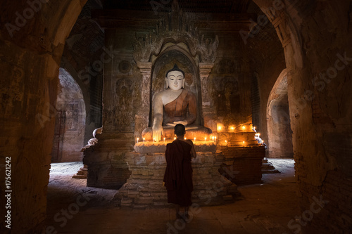 Young novice monk praying with candles in front of buddha statue inside old pagoda, Bagan Myanmar