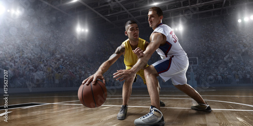 Two basketball players fight for the basketball ball on big professional arena. Player wears unbranded clothes.