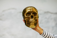 Hand Holding A Gold Skull.