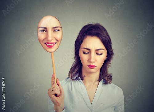 Obraz Sad young woman looking down taking off happy mask of herself - fototapety do salonu