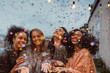 canvas print picture Four beautiful women standing at a terrace under confetti.