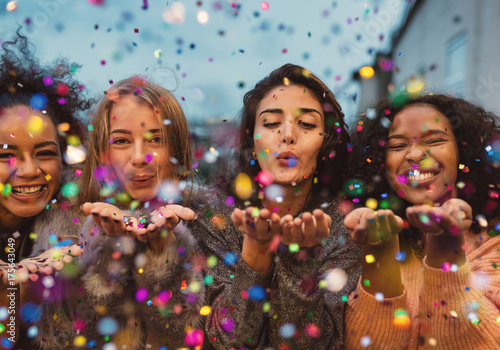 Obraz Young women blowing confetti from hands. Friends celebrating outdoors in evening at a terrace. - fototapety do salonu