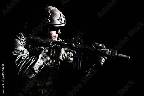 Staande foto Muziekband Half length low angle studio shot of special forces soldier in field uniforms with weapons, portrait on black background. Protective goggles glasses are on