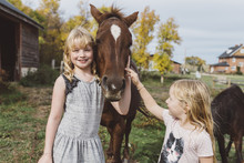 Children Standing Beside A Pony