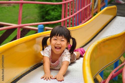Fotografia  滑り台で元気に遊ぶ女の子(夏)