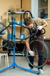 Young master in uniform fixing bolt on wheel of bicycle in workroom