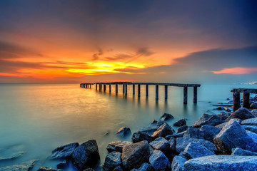 Fototapeta Minimalistyczny A long Exposure Picture Of abandoned old jetty with burning sunset as background