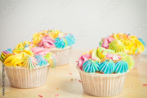 Plakat Cztery apetyczny capkakes ozdobione żółty, różowy i niebieski pokemon i dekoracje na stole na białym tle